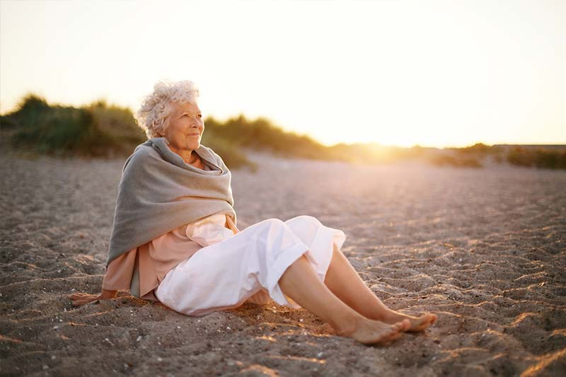 Older Woman Reflecting On The Beach