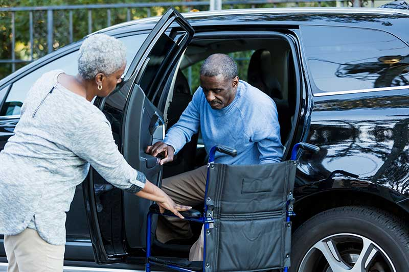 A disabled senior African American man is getting out of a car, into his wheelchair