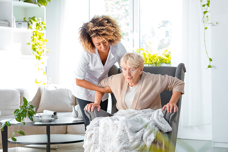 Home carer giving support of old woman to get up from an armchair in her room