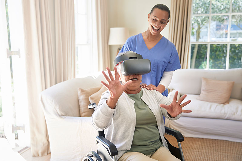 Old woman enjoying virtual reality simulator with her elder care nurse