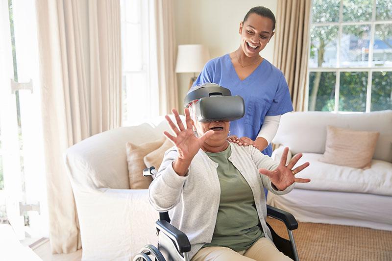 Old woman enjoying virtual reality simulator with her elder care nurse