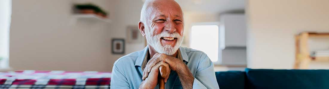 happy senior man sitting and holding his walking stick requesting in-home care
