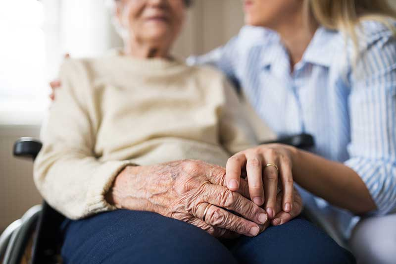 Senior woman in wheelchair getting help with the cdpap program at home